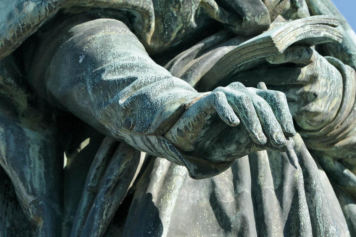 """Von der Beethoven-Statue auf dem Bonner Münsterplatz ist nur die Hand des Komponisten zu sehen, die einen Stift hält. Die Headline hierbei lautet: """"Wegweisend. Bei anspruchsvollen Vermögen."""""""